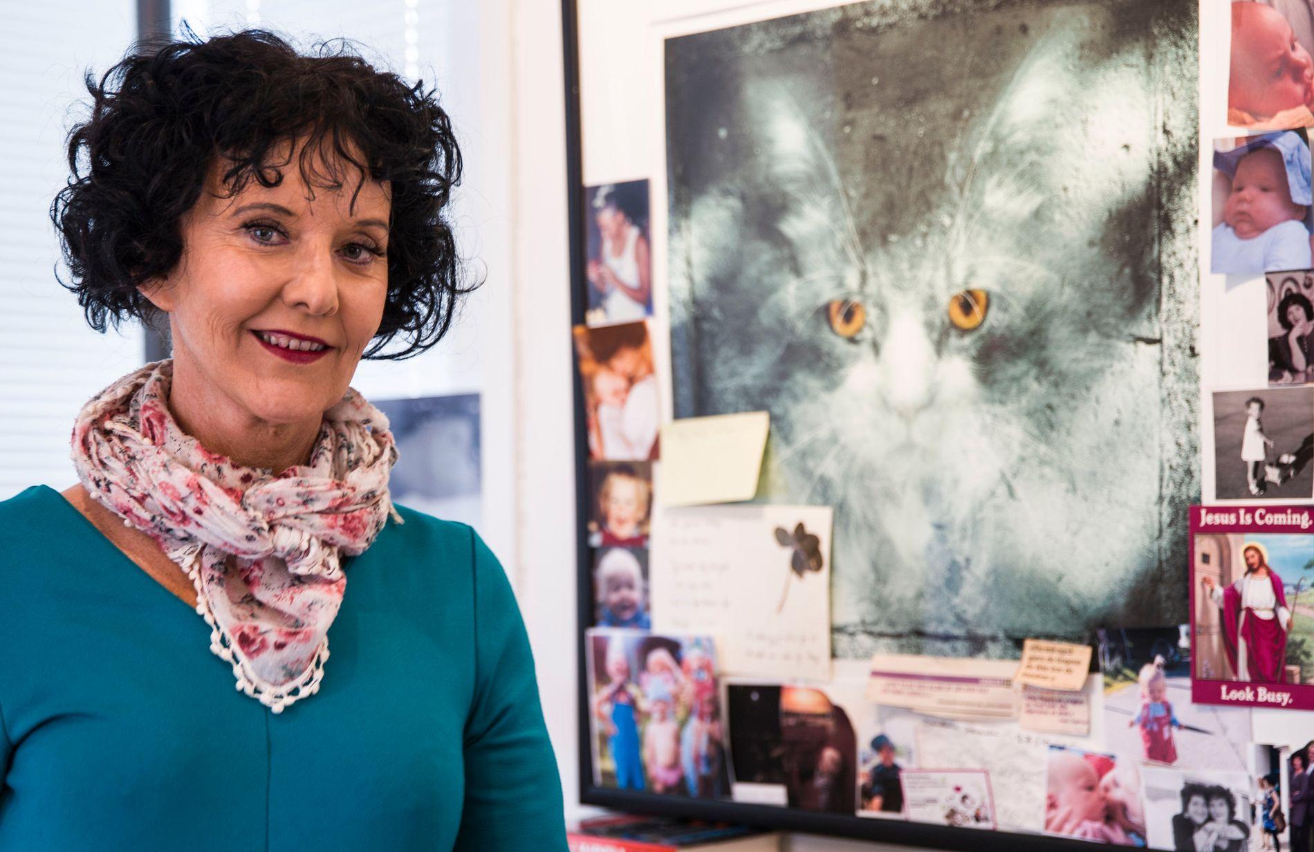 BOK OM KNUT: Unni Lindell har skrevet bok om katten Knut som hun fikk hele 18 år med. Her kikker han ned på henne fra bildet på veggen på skrivekontoret hennes.