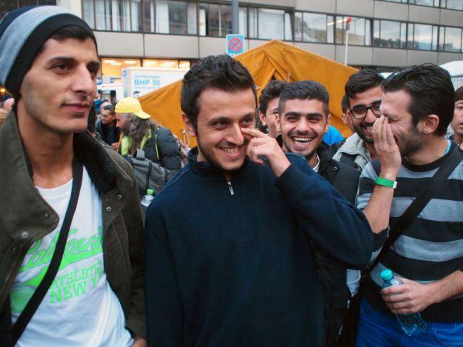 SMIL OG LATTER: Talal (i midten) og vennene hans måtte le da de så hvordan de ble tatt imot utenfor jernbanestasjonen i München. I sterk kontrast til hva de opplevde i Budapest.
