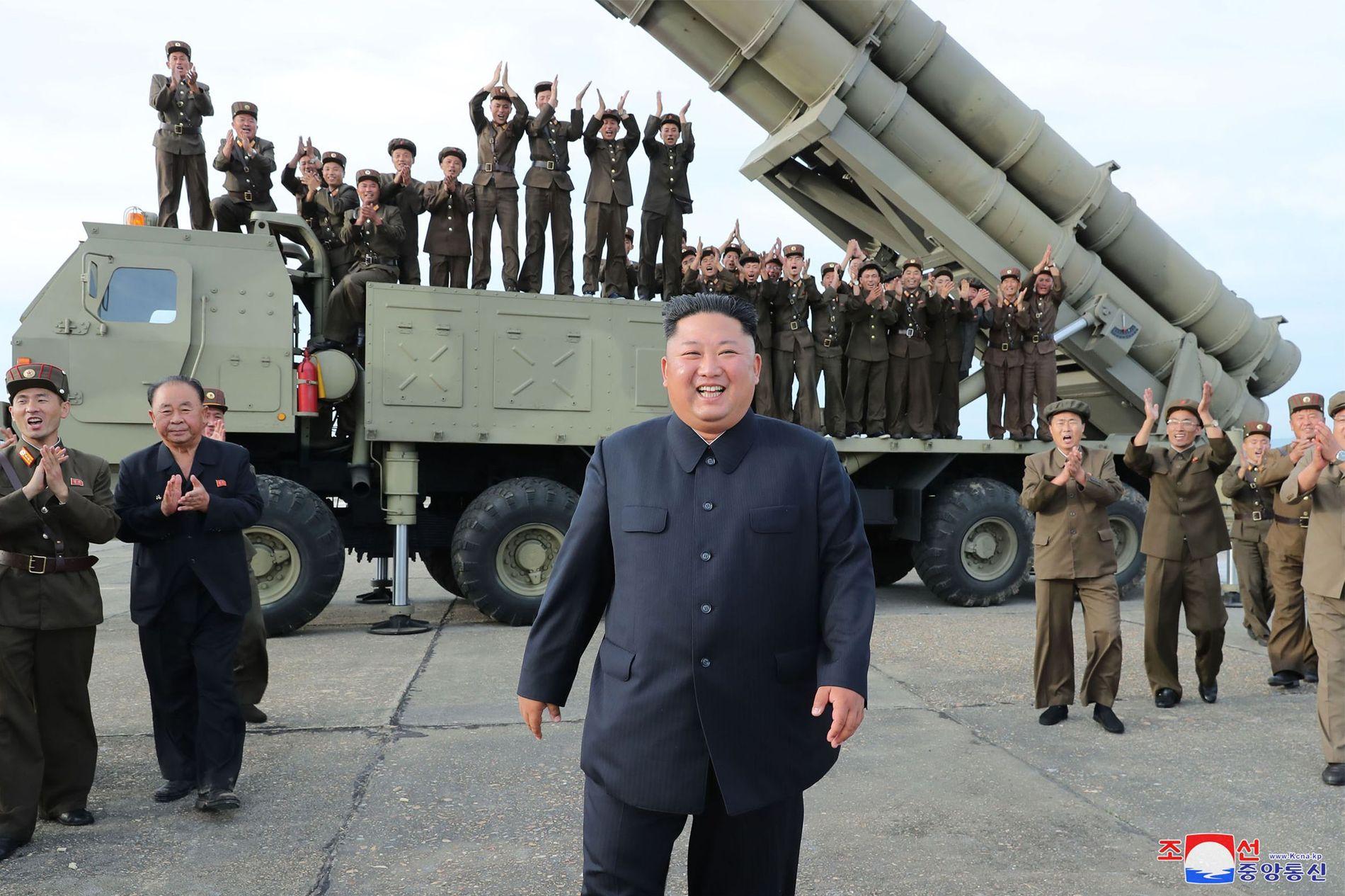 GODT FORNØYD: Nord-Koreas Kim Jong-un på bildene frigitt søndag. Ifølge landets statlige nyhetsbyrå feirer de her en vellykket rakettopskyting.