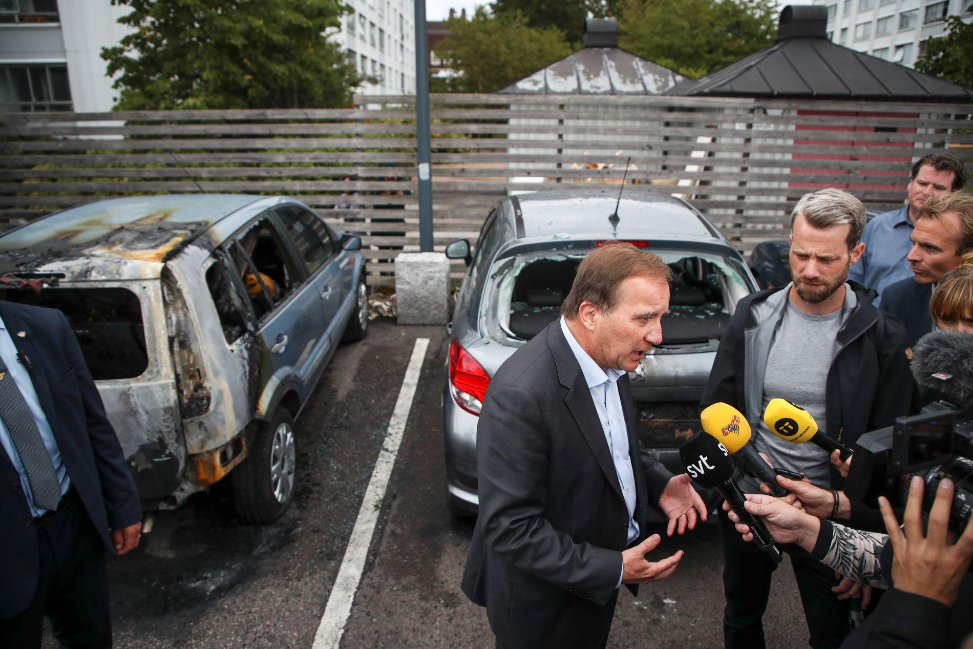 BILBRANNER: Sveriges statsminister Stefan Löfven svarer på spørsmål fra reportere på Frölunda torg i Göteborg, etter mandagens mange påsatte bilbranner i byen.
