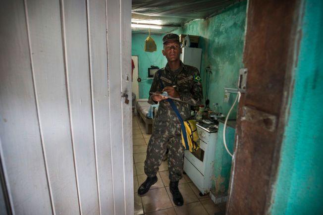 PÅ JAKT: Mauricio (20) fra den brasilianske hæren inspiserer huset til Genivaldo (56) i slummen i Monteiro, Recife.