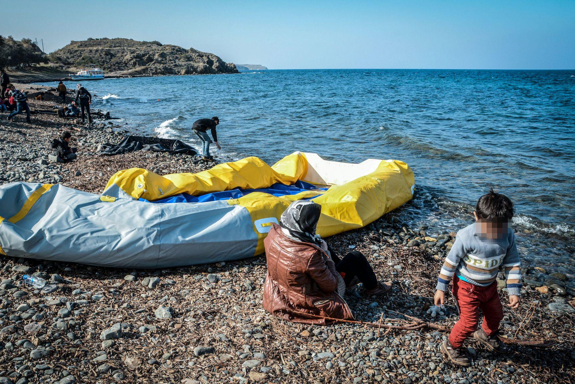 KOM SJØVEIEN: Et barn leker i vannkanten ved siden av en gummibåt som har fraktet asylsøkere til den greske øya Lesvos.