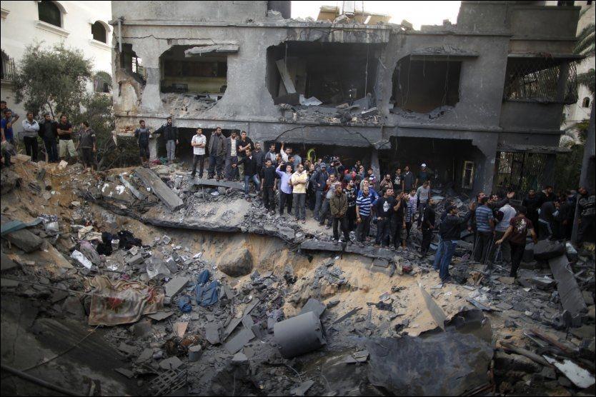 I RUINNER: Naboer samler seg rundt ruinene av huset som ble truffet under israelske luftangrep søndag. Foto: REUTERS