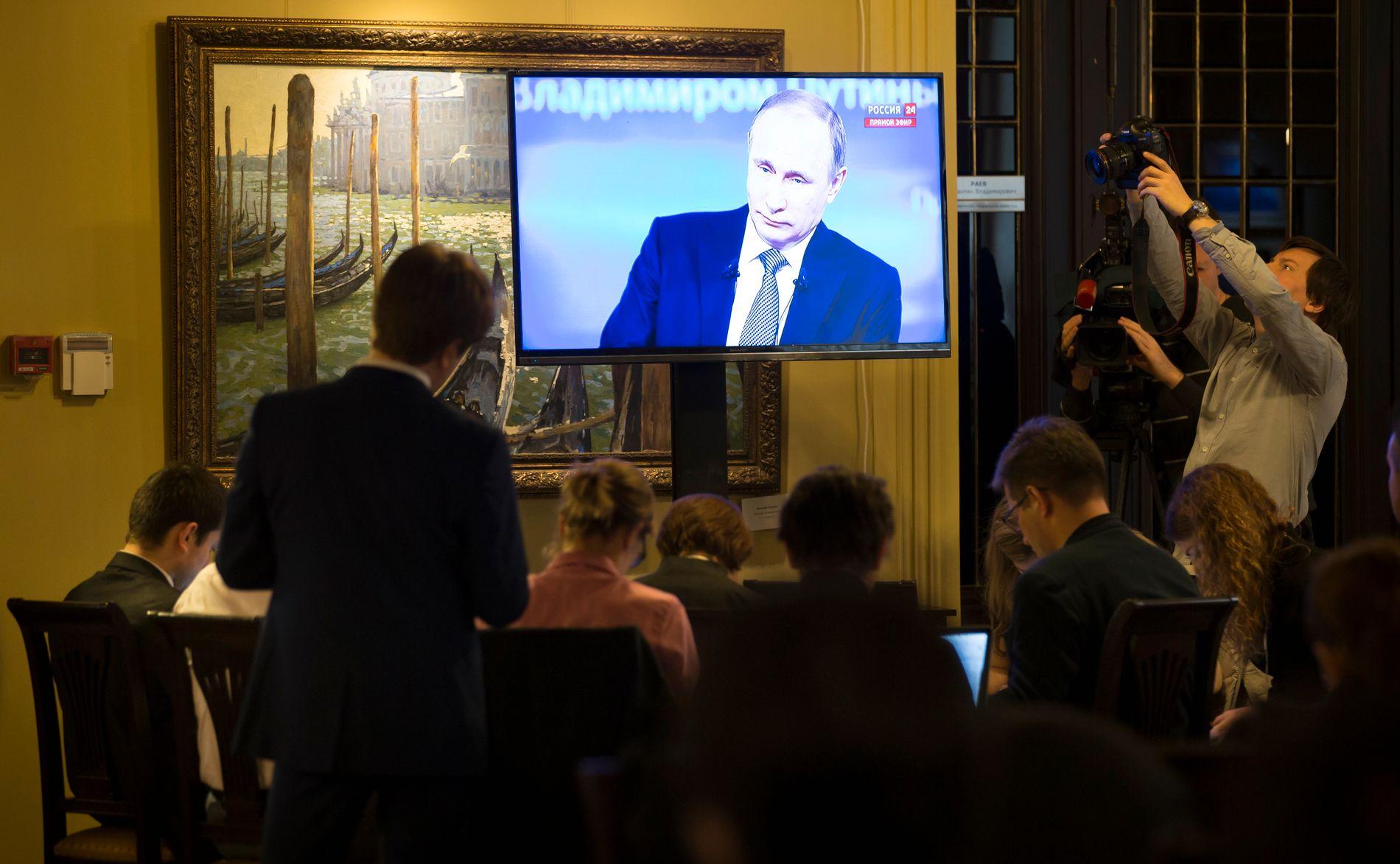 NOTERER: Journalister i Moskva ser på TV mens den russiske presidenten Vladimir Putin snakker under sin årlige innringningsseanse.