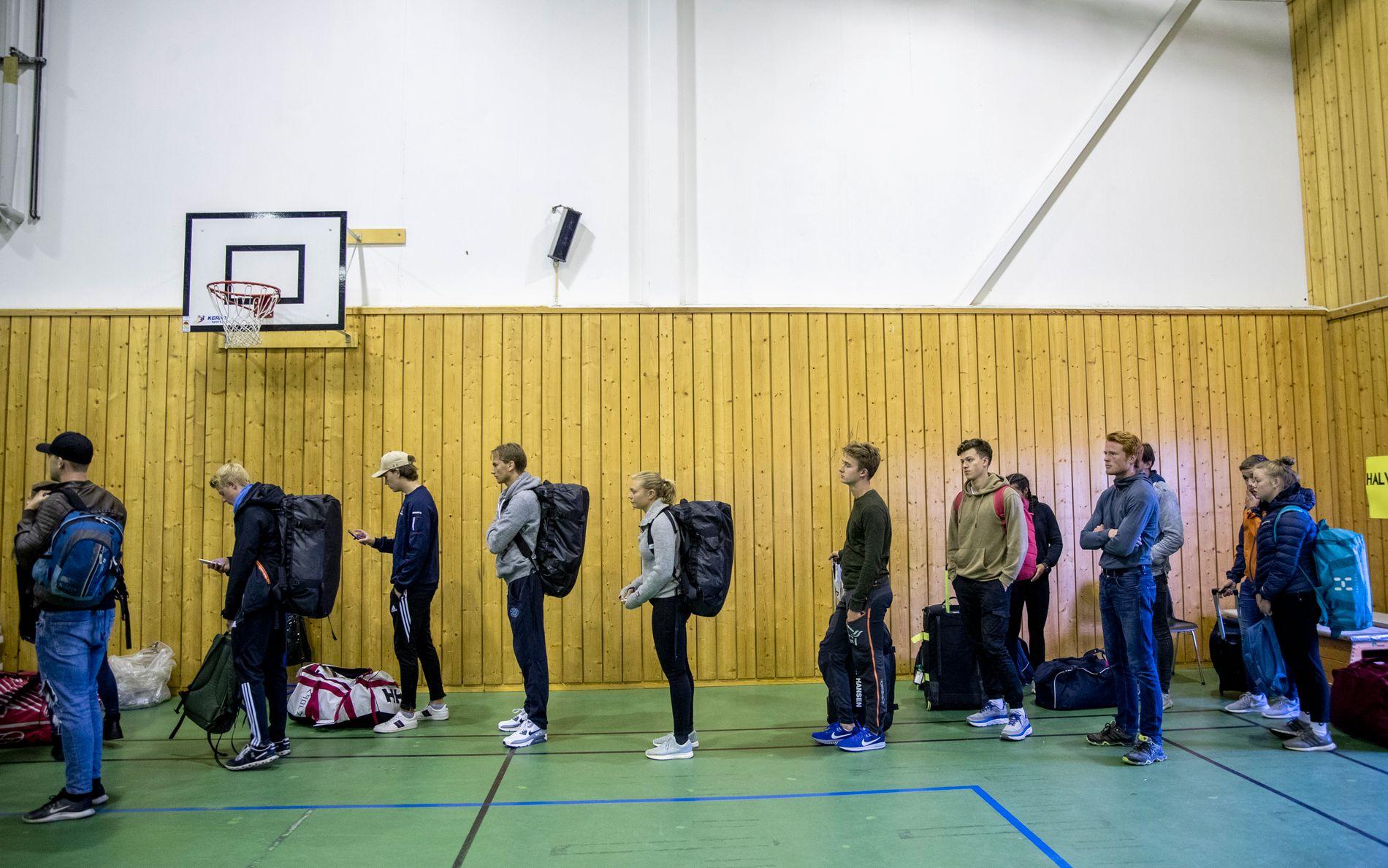 MYE VENTING: Trym Hallingby og Hedda Horn Rønneberg, begge i grått, venter på å registrere seg som oppmøtt på innrykk.