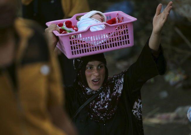 FORTVILER: En av innbyggerne fra Ramadi bærer barnet sitt i en kurv på hodet i utkanten av Bagdad. Andre er ikke like heldige: Flere tusen flyktninger får ikke komme inn i  hovedstaden, og lever nå utendørs i ørkenen.