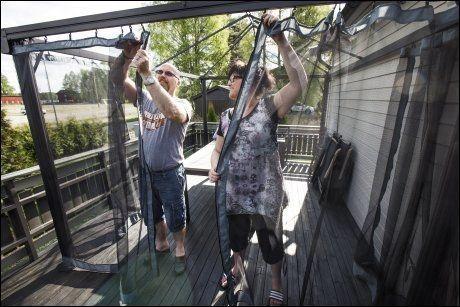 Ivar og Anita Lofthus trekker myggnetting rundt paviljongen på terrassen. Så skal det duk utenpå. Paret vet å beskytte seg mot myggen. Foto: FRODE HANSEN