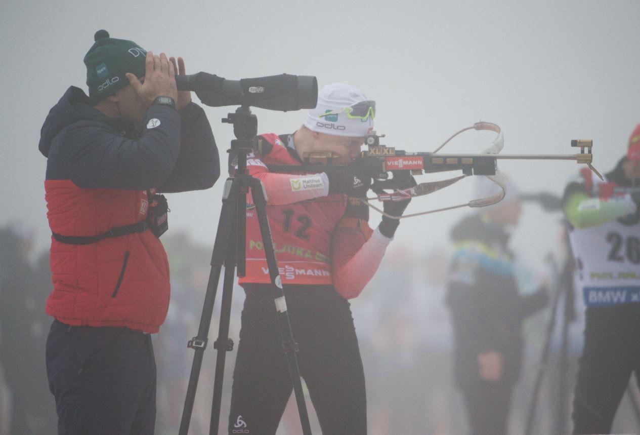 I TÅKEN: Johannes Thingnes Bø forsøker å treffe blinkene i tåken i Pokljuka. Trener Siegfried Mazet (t.v.) har også tatt plass på matten på standplass for i det hele tatt se hvor skuddene sitter.
