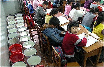 BØTTEVIS: Bakerst i klasserommet på en barneskole i Harbin står bøtter med vann på rekke og rad. Foto: Reuters