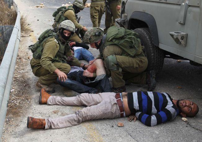 TRE PÅGREPET: Israelske soldater gir førstehjelp til tre av de palestinske demonstrantene som ble pågrepet etter onsdagens uroligheter ved Beit El.