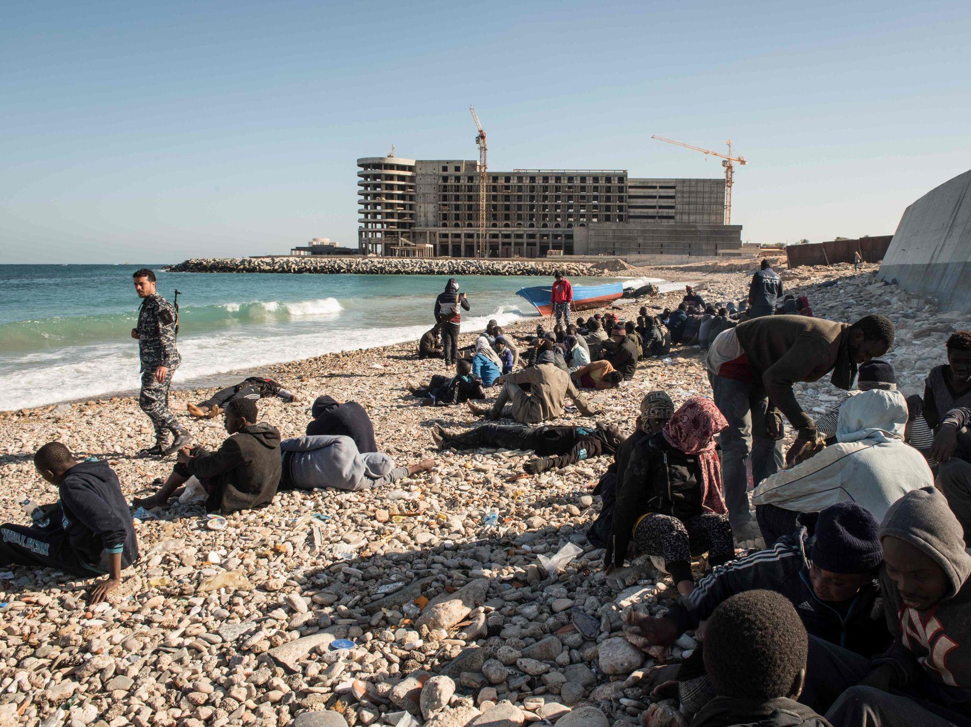 TRAGISK: En gruppe menn, flesteparten fra Senegal, på stranden utenfor Libyas hovedstad Tripoli i jauar 2017. Flyktningene dro fra kystbyen Sabratha. Etter flere dager på sjøen så de omsider land og trodde det var Italia. Flere druknet da de forsøkte å svømme i land. Foto: AFP