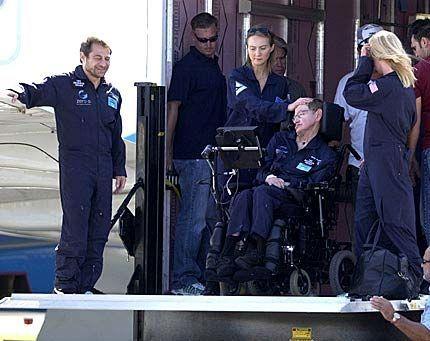 ETTER TUREN: Lederen for Zero Gravity Corp., Peter Diamandis (t.v.), ser på mens den lamme astrofysikeren Stephen Hawking blir assistert ut av flyet etter å ha fått oppleve hele fire minutter med vektløshet. Foto: AP