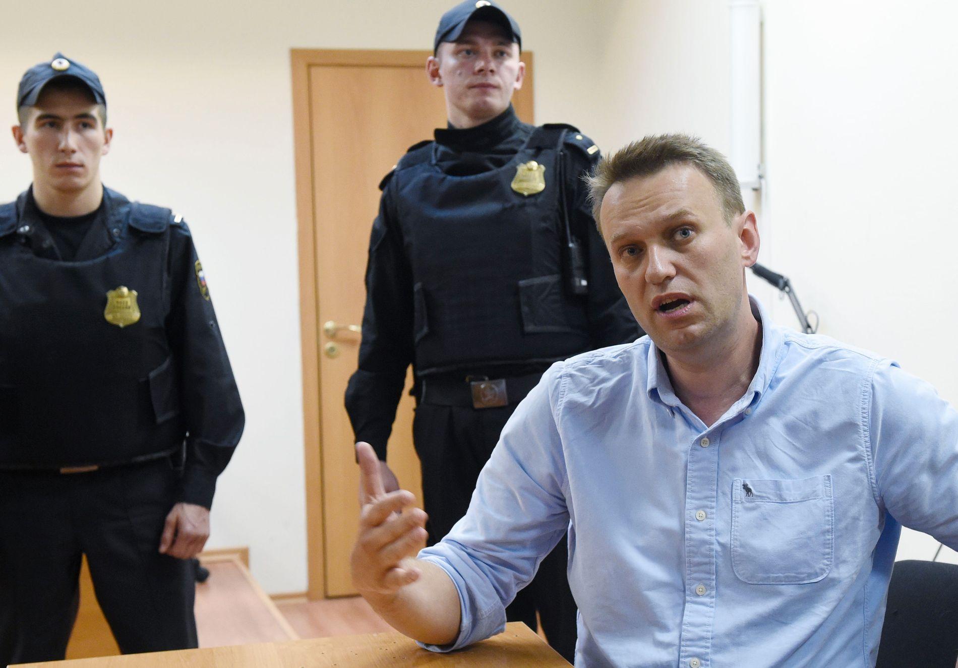 I VARETEKT: Navalnyj snakker fra varetekt mandag kveld etter å ha blitt hanket inn av politiet, beskyldt for å arrangere en ulovlig demonstrasjon. FOTO: AFP