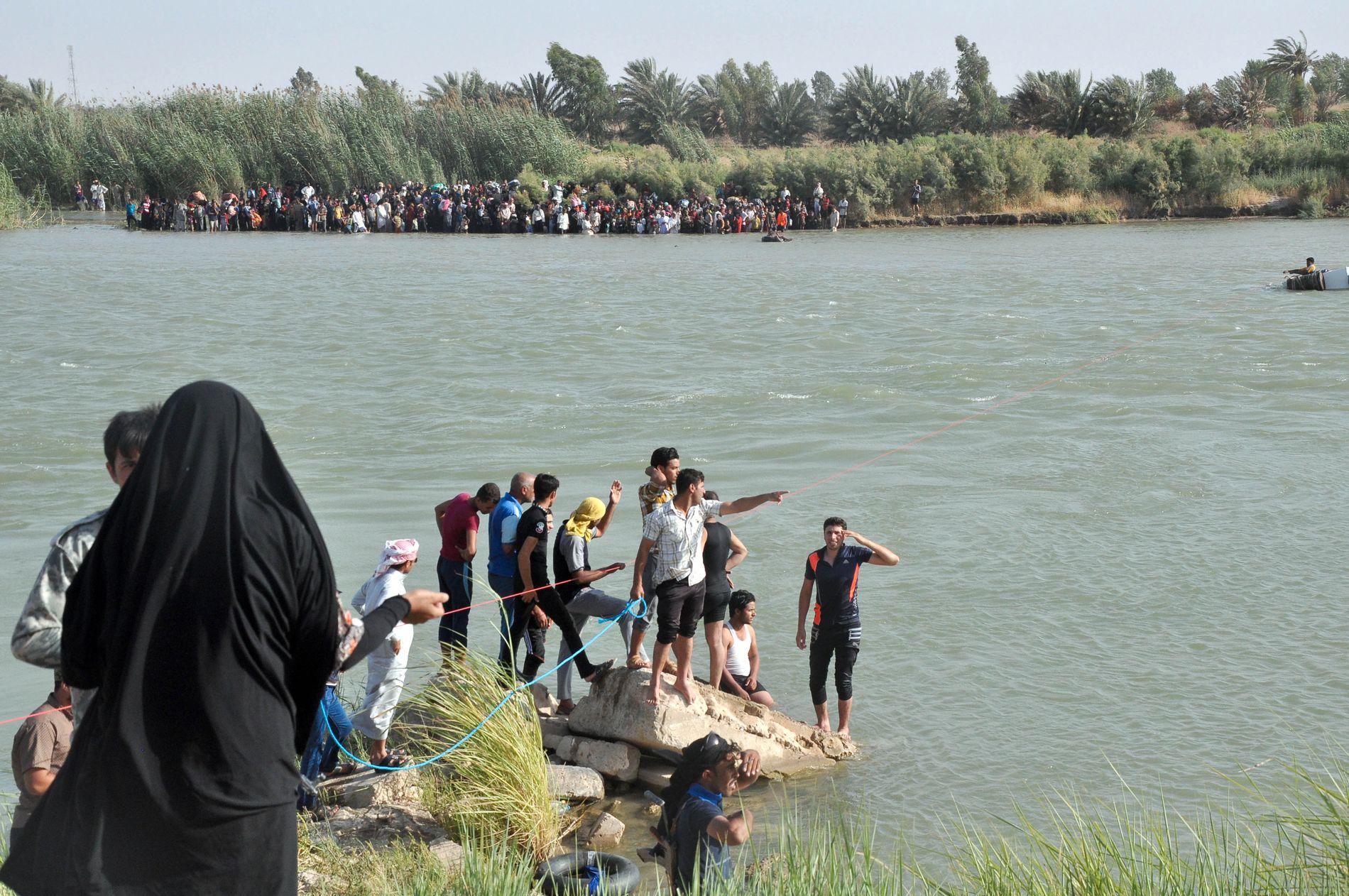 PÅ FLUKT: Sivile står ved Eufrats bredder. De må krysse elven for å komme seg bort fra krigshandlingene i Fallujah. Bildet er tatt 2.juni.