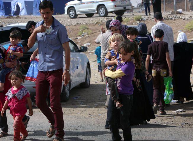 PÅ FLUKT: Rundt en halv million irakere, halvparten av dem barn, er på rømmen fra de voldelige opprørerne. Her forsøker en familie å komme seg ut av Nineveh-provinsen torsdag.