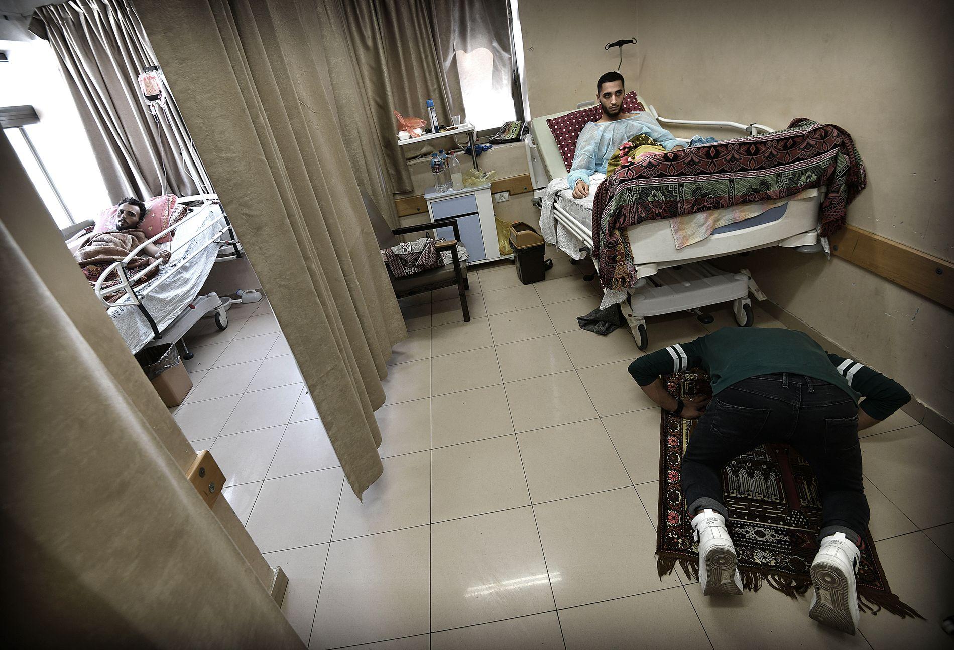 PROTEST-PASIENTER: Naser al-Shorbaji (24) mistet mye blod å vei til sykehuset etter å ha blitt skutt ved grensegjerdet. Broren Mohammed (22) ber foran sykesengen, og i rommet ved siden av ligger Mohammed al-Sirzawy (27), som er blitt skutt i venstre lår.
