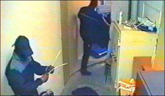 RANSDØMT: Lars Harnes og to andre ranere truet vektere med en maskinpistol under ranet av DNBs filial på Aker Brygge 30. august 2004. Den ene raneren på vei ut av rommet med 2,6 millioner mens Lars Harnes gjør klar strips til å binde den andre vekteren. Foto: DnB