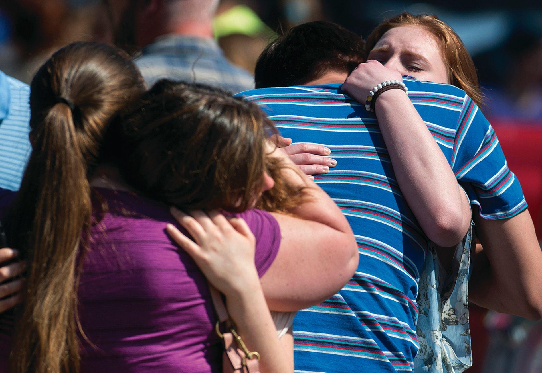 BEKYMREDE FORELDRE: Barne klemmer sine foreldre idet de kommer ut av skolebygningen.