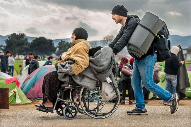 FAMILIEFLUKTEN: Dette er et stadig vanligere syn på veien mot Europa, ifølge hjelpeorganisasjonene. Med hele familier på flukt, går andelen menn blant flyktningene og migrantene ned. Denne familien er på vei inn i dager i usikkerhet i Idomeni-leiren nord i Hellas.