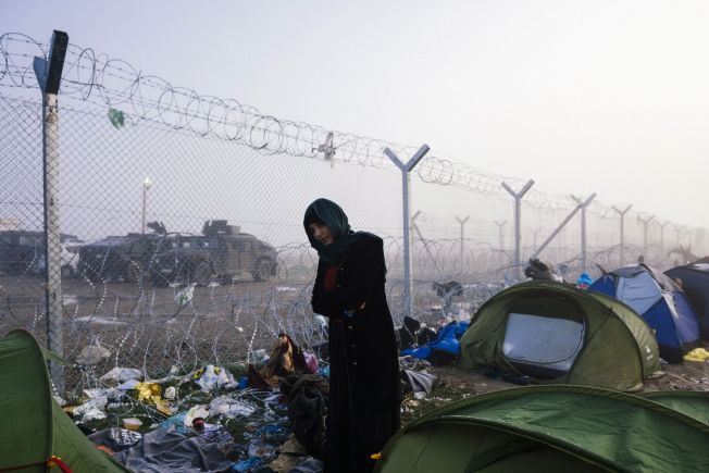 HØYE GJERDER: På grensen mellom Hellas og Makedonia slipper kun noen syrere og noen irakere gjennom, mens afghanere og alle andre nasjonaliteter blir holdt igjen. Grenserestriksjonen har ført til at titusenvis av flyktninger og migranter er strandet i Hellas, uten å kunne dra videre.