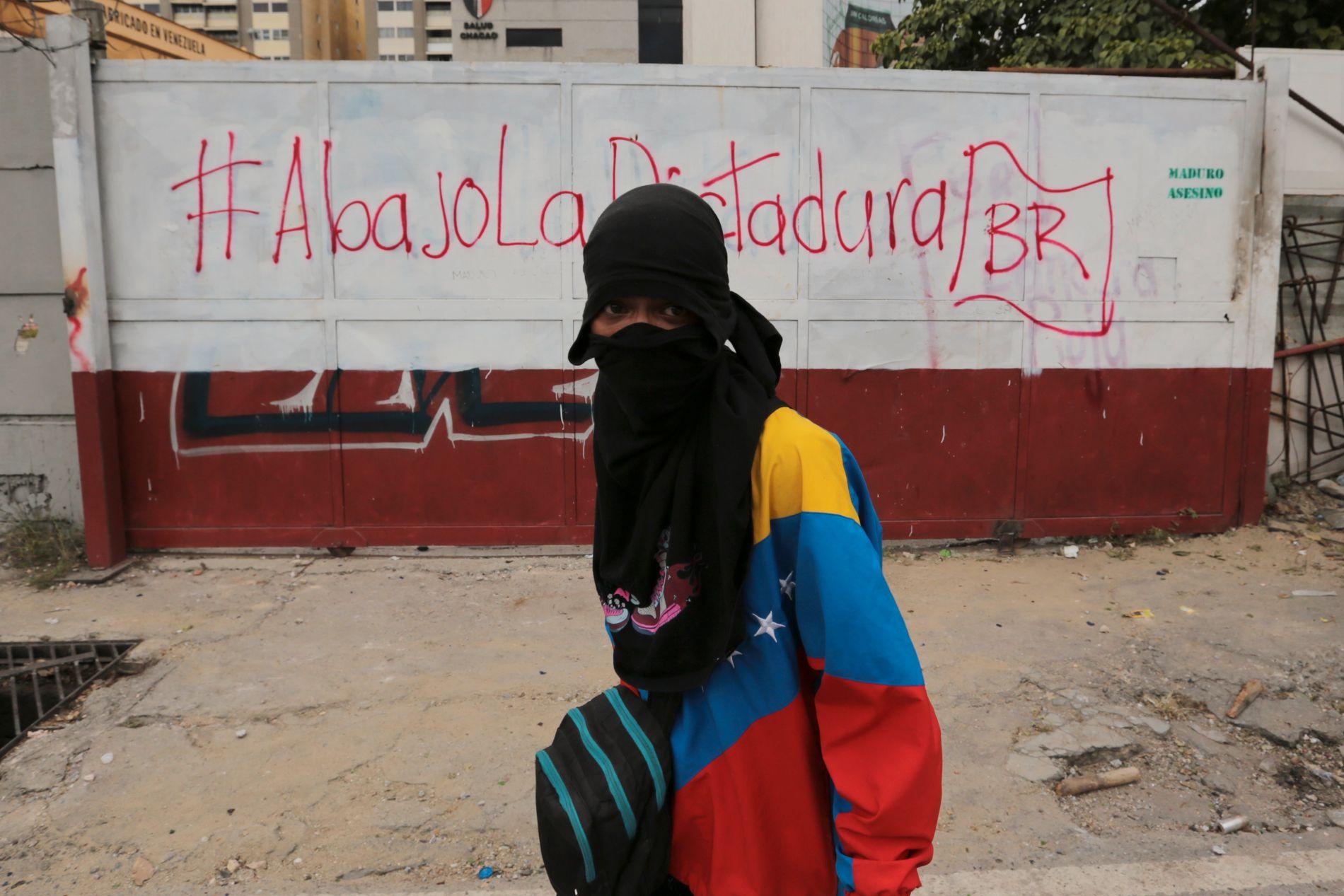 KRISE: En maskert anti-regjeringsdemonstrant i Caracas foran en grafitti der det står skrevet «ned med diktaturet» og «Maduro, morder».