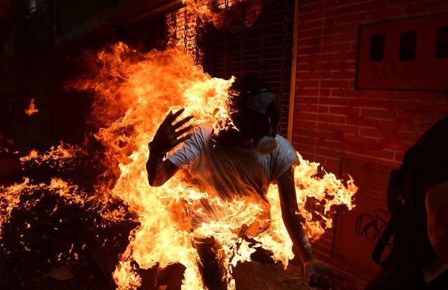 TAR FYR: En demonstrant tar full fyr i voldelige demonstrasjoner i starten av mai. Mannen skal ha overlevd, ifølge fotografen.