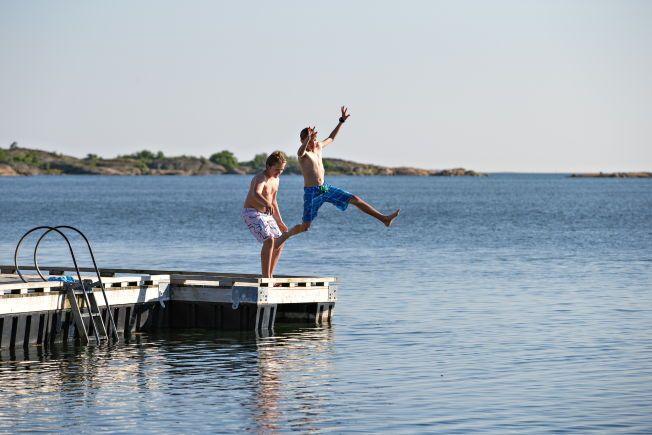 SOMMERBAD: Nicolay Alexander Carlsen og Sebastian Søland Dyrbing, begge 12 år hopper i vannet i Enhuskilen på Kråkerøy. FOTO: GISLE ODDSTAD/VG