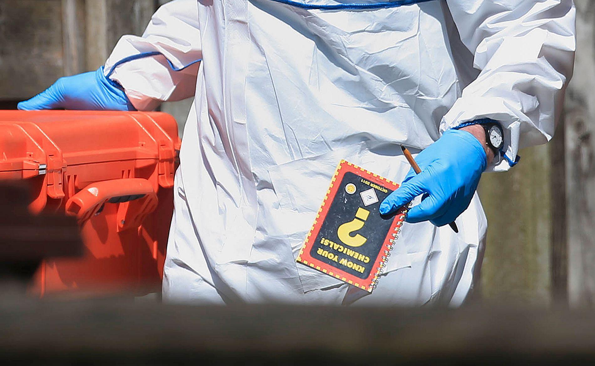FANT BOK: Krimteknikere kommer her ut av boligen til Salman Abedi med en bok kalt «Know your chemicals».
