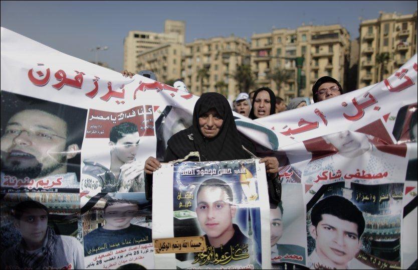 MISTET MANGE: Egyptiske demonstranter holder bannere som viser bilder av personer drept i sammenstøt med sikkerhetsstyrker, på Tahrir-plassen mandag 23. januar 2012. Foto: AP Photo/Muhammed Muheisen