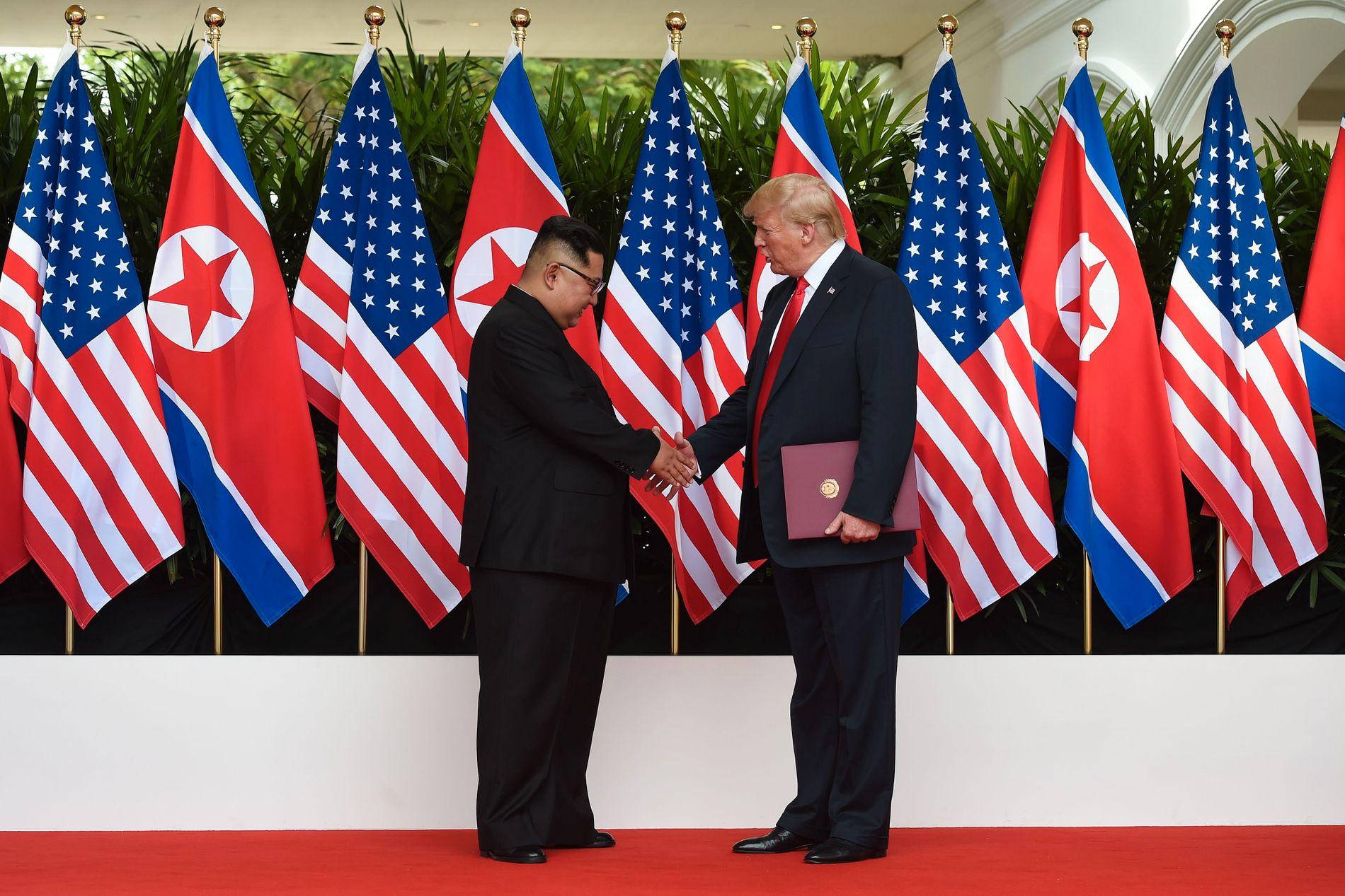 HEI: Donald Trump og Kim Jong-un håndhilser som en del av underskrivelsesseremonien.