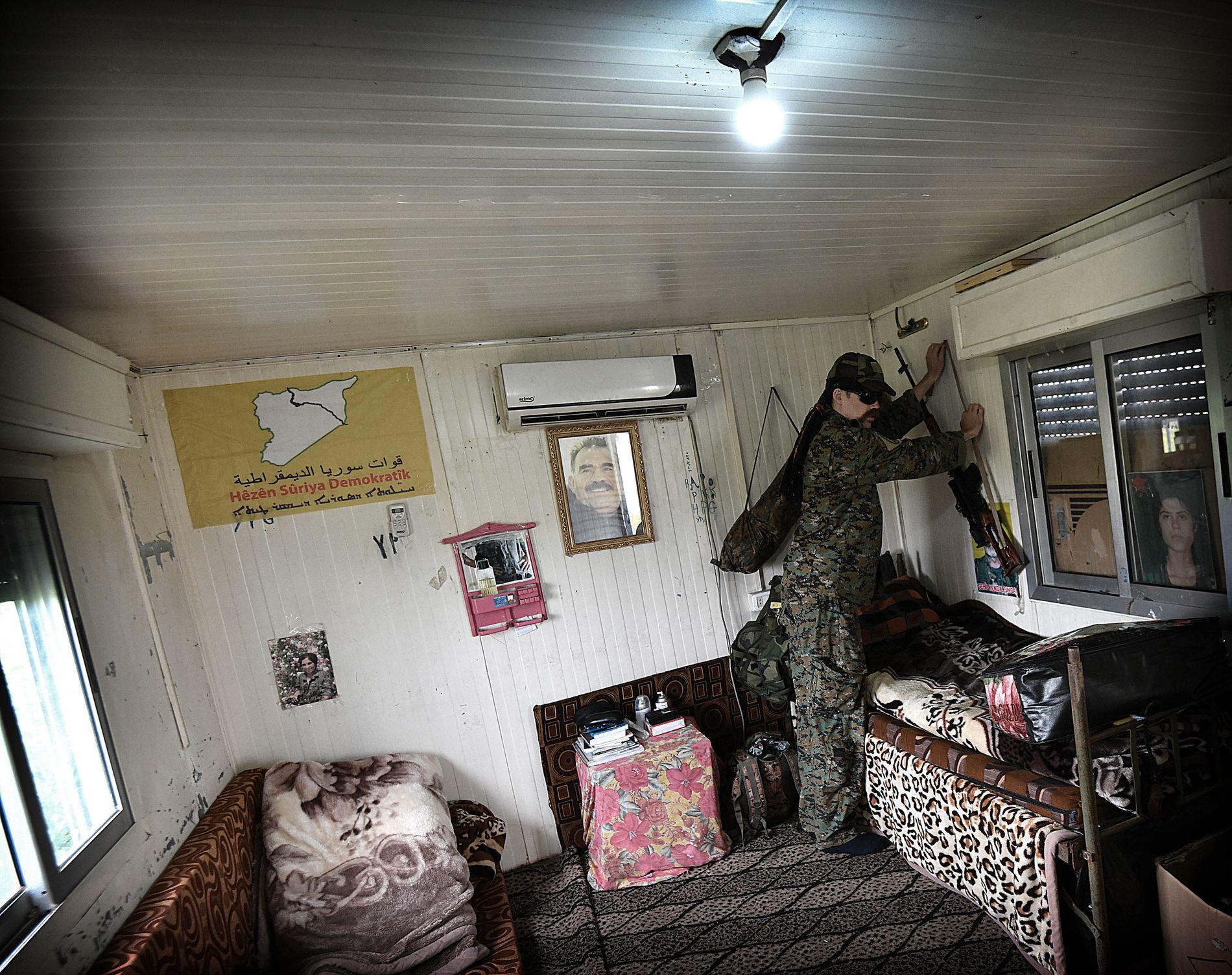 SOVEROM: På rommet til Gulbrandsen, bak våpenet han henger opp, er en plakat med bilde av vennen som ble drept i IS-angrepet i august.