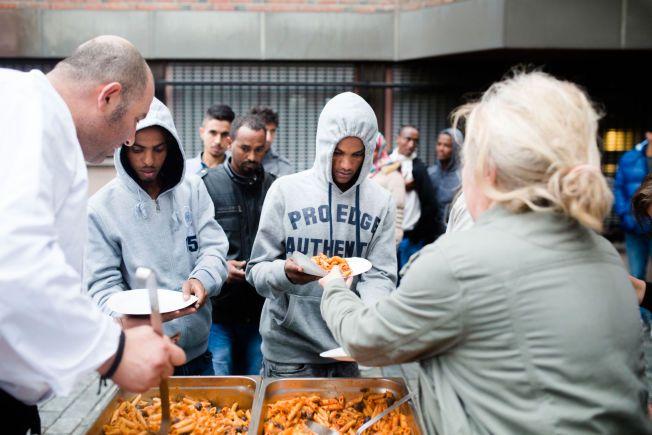 DELER UT MAT: Frivillige deler ut mat til nyankomne asylsøkere ved Politiets utlendingsenhet på Tøyen.