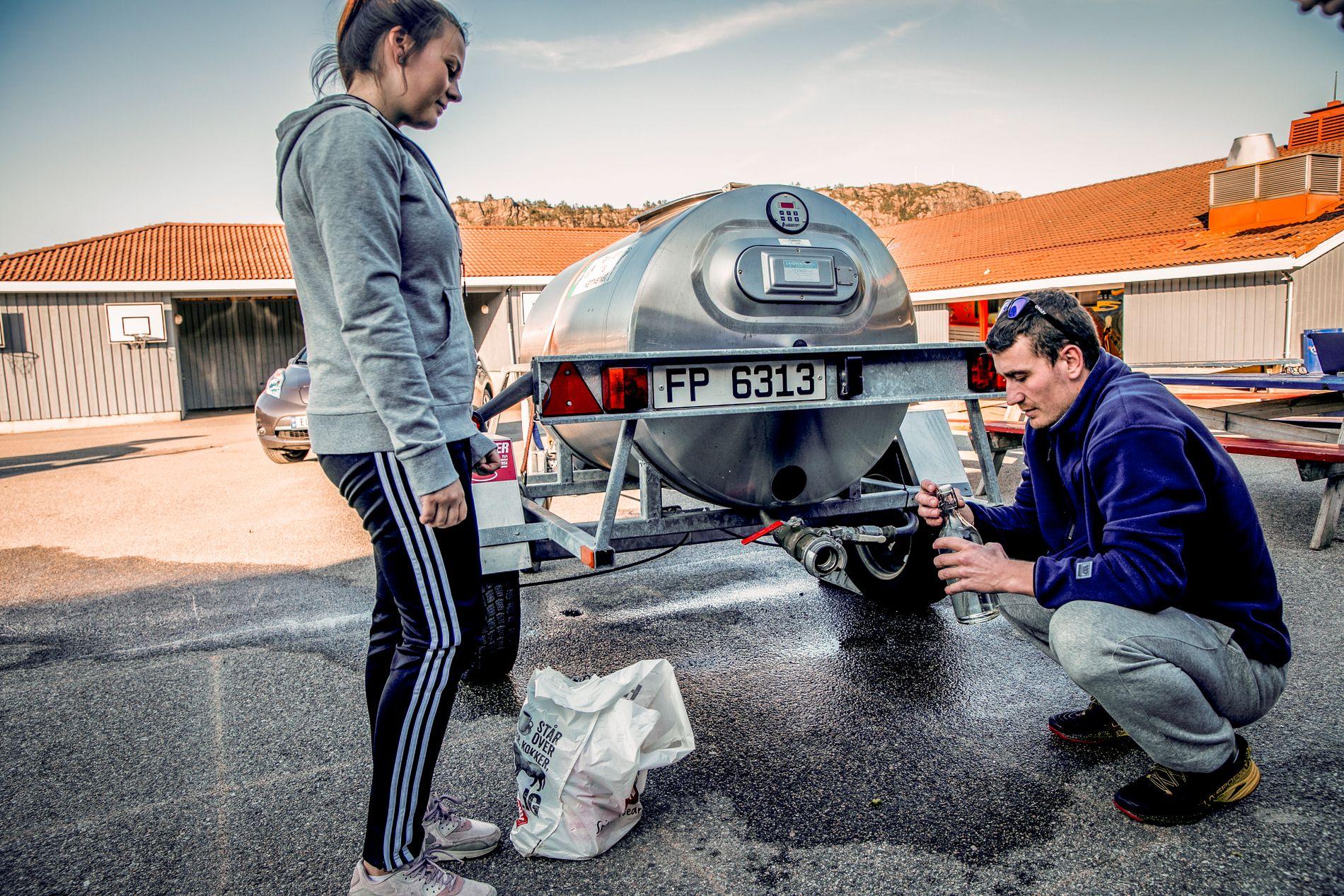 FYLLER VANN: Daniel Følling (29) og Karoline Bekkenes (22) henter vann på en vannstasjon kommunen har satt opp. De bor i området der flest har vært smittet.