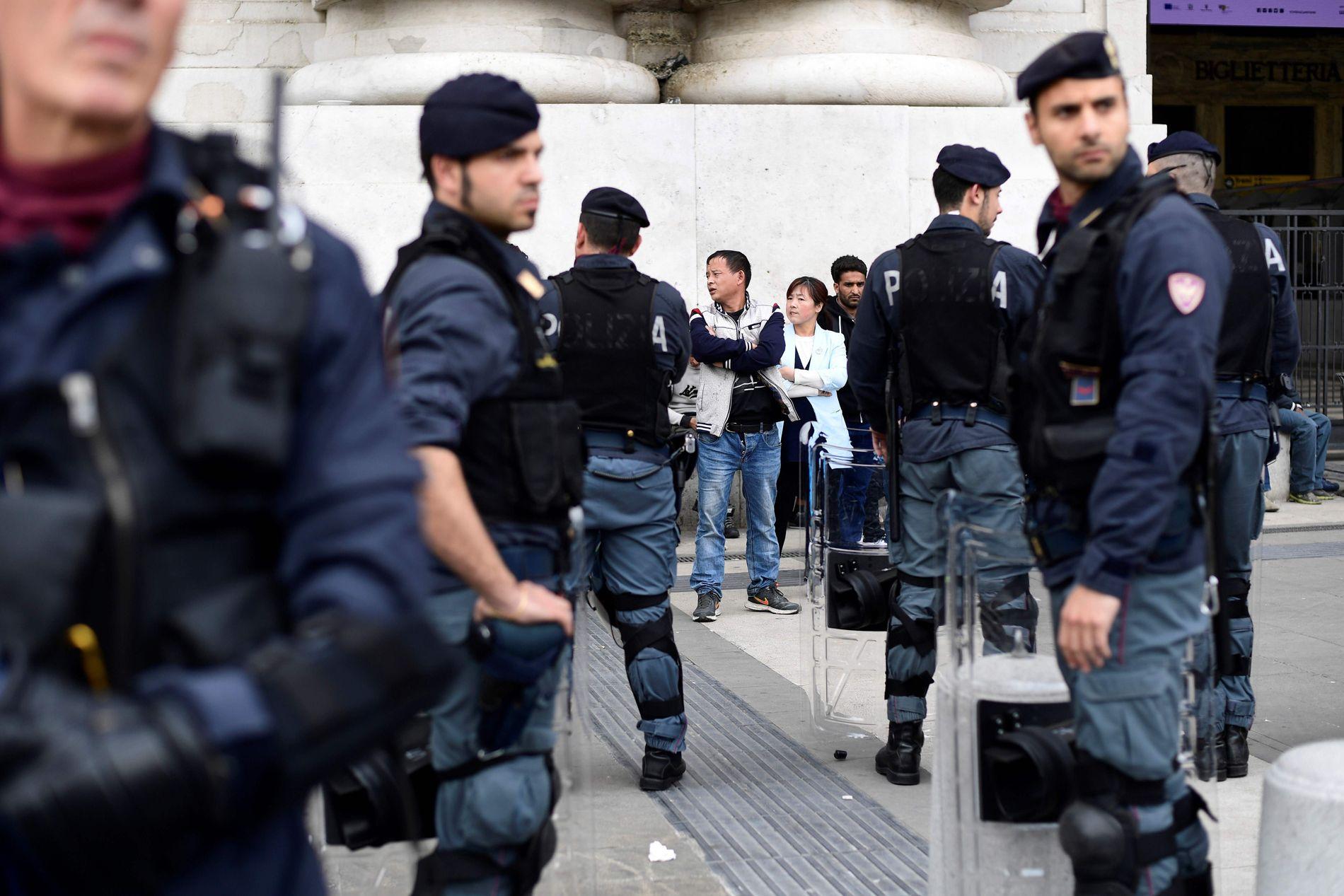 ID-KONTROLL: Italienske politibetjenter kontrollerer identiteten til immigranter på sentralstasjonen i Milano. Italia står midt i en migrasjonskrise. Ikke en flyktningkrise. Svært få av de nærmere 100000 menneskene som har kommet over Middelhavet til Italia siden årsskiftet, har beskyttelsesbehov som gir grunnlag for opphold. FOTO: AFP