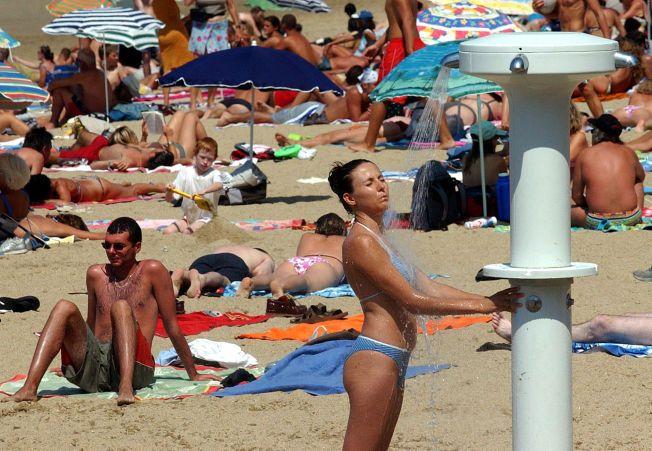 HETE-KATASTROFE: Mer enn 72 000 mennesker døde under hetebølgen i Sentral-Europa i august 2003. I alt 138 000 har omkommer i hetebølger i Europa etter tusenårsskiftet. Her tar en kvinne kjølende dusj på stranden i Biarritz i Sør-Frankrike 19. august 2003.