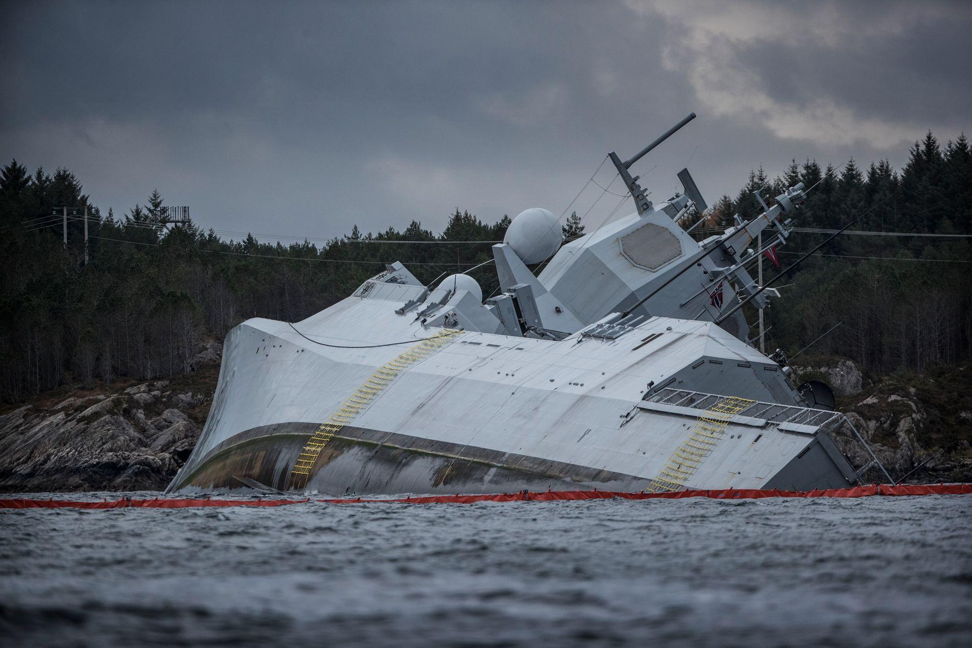 KRENGET: Det store fregattskipet KNM Helge Ingstad ligger med en kraftig krengning inn mot land - med et tynt lag med olje og lenser rundt skipet.