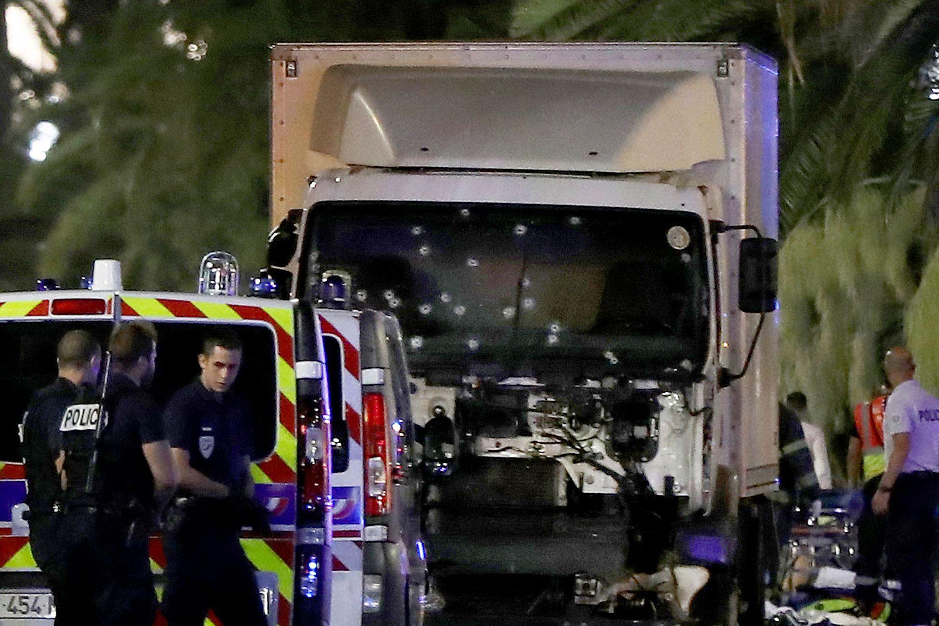FLERE HULL I LASTEBILEN: Politiet står ved lastebilen som kjørte inn i en folkemengde langs strandpromenaden i Nice torsdag kveld. Vinduet foran er dekket med skuddhull.