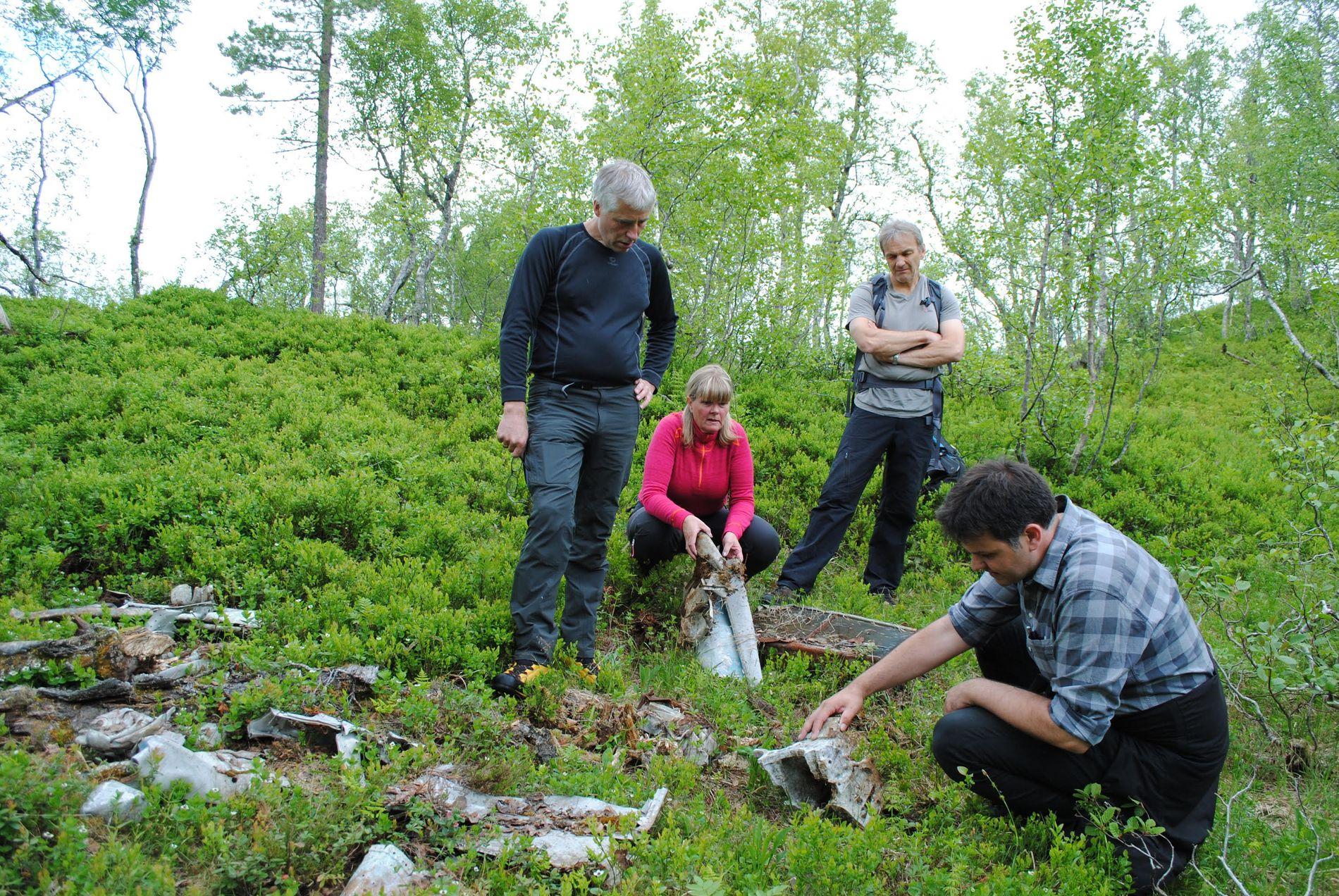 I FELT: Frode Foss, Lilli Husby og Råg Ranes fra Surnadal sammen med Tony Hoskins (sittende til høyre) i myrlandskapet der flyet har ligget i årtier.