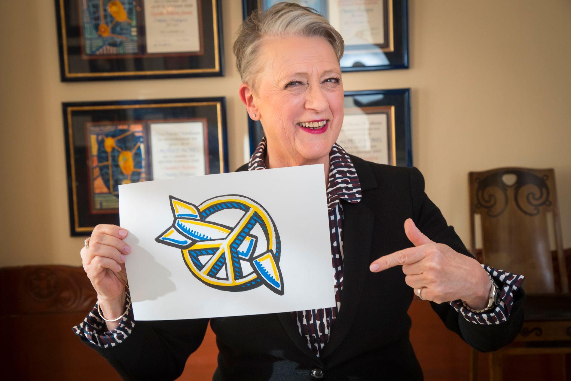 GA NOBELPRISEN TIL ICAN: Berit Reiss-Andersen, leder av Nobelkomiteen, med en tegning av logoen til Den internasjonale kampanjen for forbud mot atomvåpen.