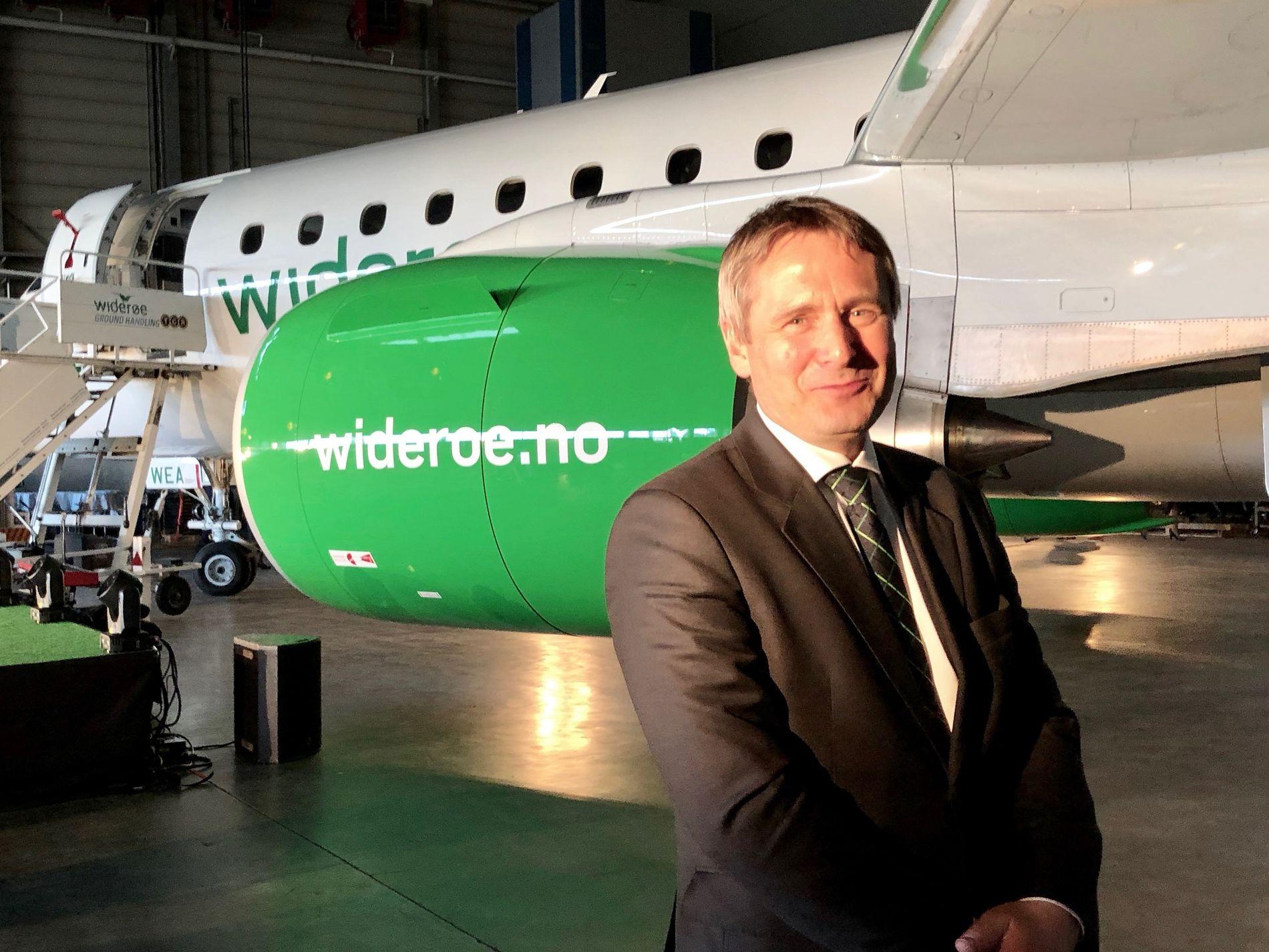 Widerøe-sjef Stein Nilsen avbildet foran det splitter nye jetflyet Embraer E2-E190