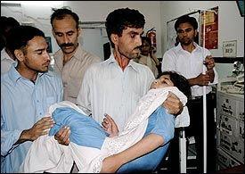 FLERE SKADD: En pakistansk mann bærer en jente, som ble skadet da en vegg på skolen hennes raste ned i jordskjelvet i dag. Foto: AFP