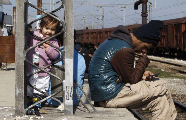 PÅ FLUKT: Et barn og en mann ved et transittsenter for flyktninger i Makedonia. De venter på tillatelse til å krysse grensen til Serbia.