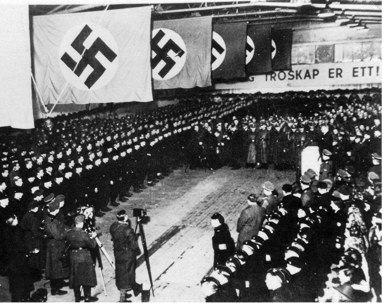 VILLE SLÅSS FOR HITLER: Oppstilling for norske rekrutter som har vervet seg som frivillige til Wafffen-SS og 5. SS-Division Wiking. Hippodromen på Vinderen i Oslo er pyntet. Hirden og tyske soldater står æresvakt. Pressen er også til stede. Foto: FRA «DERES ÆRE VAR TROSKAP»/VEGA FORLAG/GEIR BRENDENS ARKIV