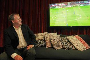 FOTBALLMANN: Yngve Hallén ser alvorlig på situasjonen i FIFA, men trekker på smilebåndet når han ser at delegathotellet endelig har fått fotball på TV-en.