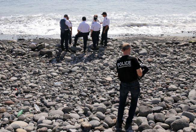 UNDERSØKER: Politimenn undersøker området på øya Réunion i Det indiske hav. Søndag ble en flydør funnet på øya, bare dager etter funnet av en vingeklaff. Her undersøker politiet en metalldel som foreløpig ikke er bekreftet å stamme fra et fly.