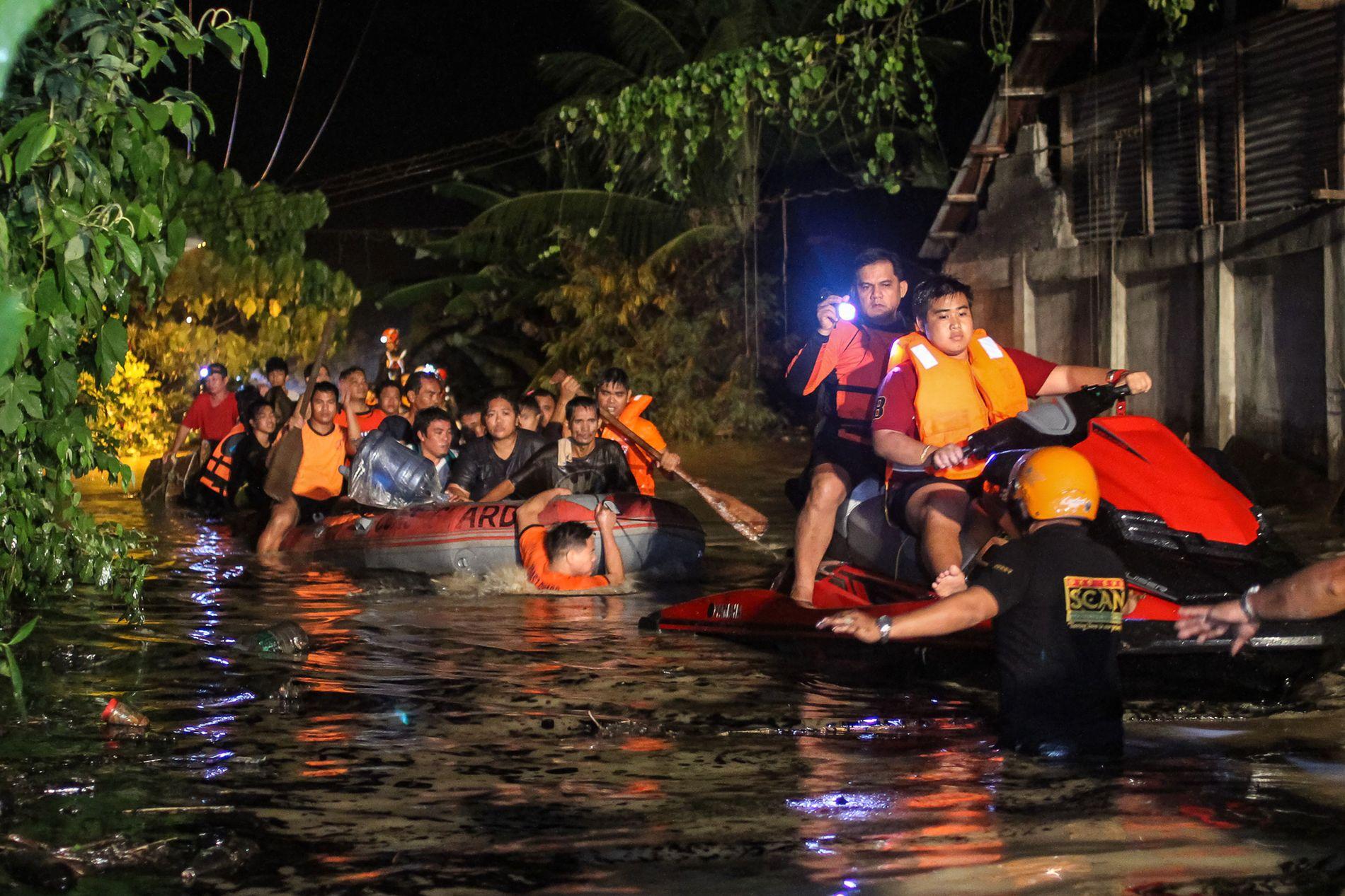EVAKUERES: Redningsarbeidere evakuerer flomrammede innbyggerne i den Filippinske byen Davao på lørdag. Nå er uværet på vei til Vietnam