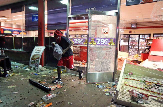ØDELEGGELSER: En mann forlater en butikk i Ferguson, sent søndag kveld amerikansk tid. Flere butikker i byen er blitt plyndret under opptøyer som brøt ut etter en minnestund for den amerikanske tenåringen Michael Brown, som skal ha blitt skutt av politiet lørdag.