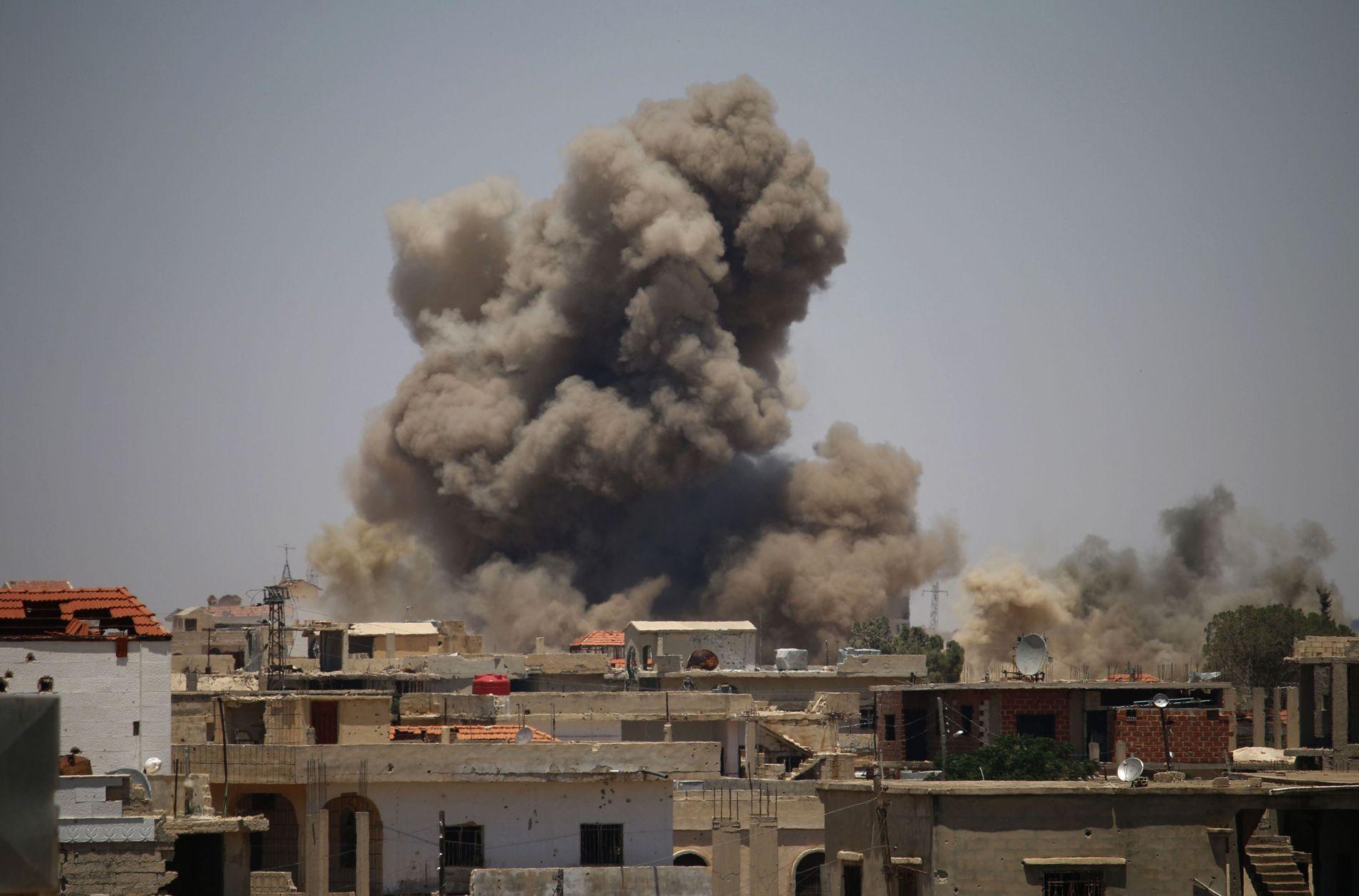BOMBEREGN: Røyk stiger opp etter et bombeangrep utført av syriske regjeringsstyrker i Daraa den 24. juni.