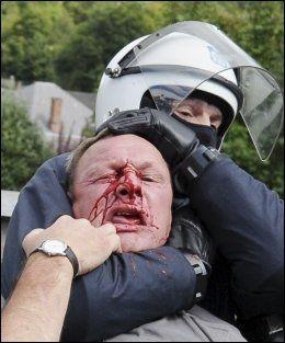 BLODIG: En politimann arresterer en mann utenfor klosteret. Foto: REUTERS