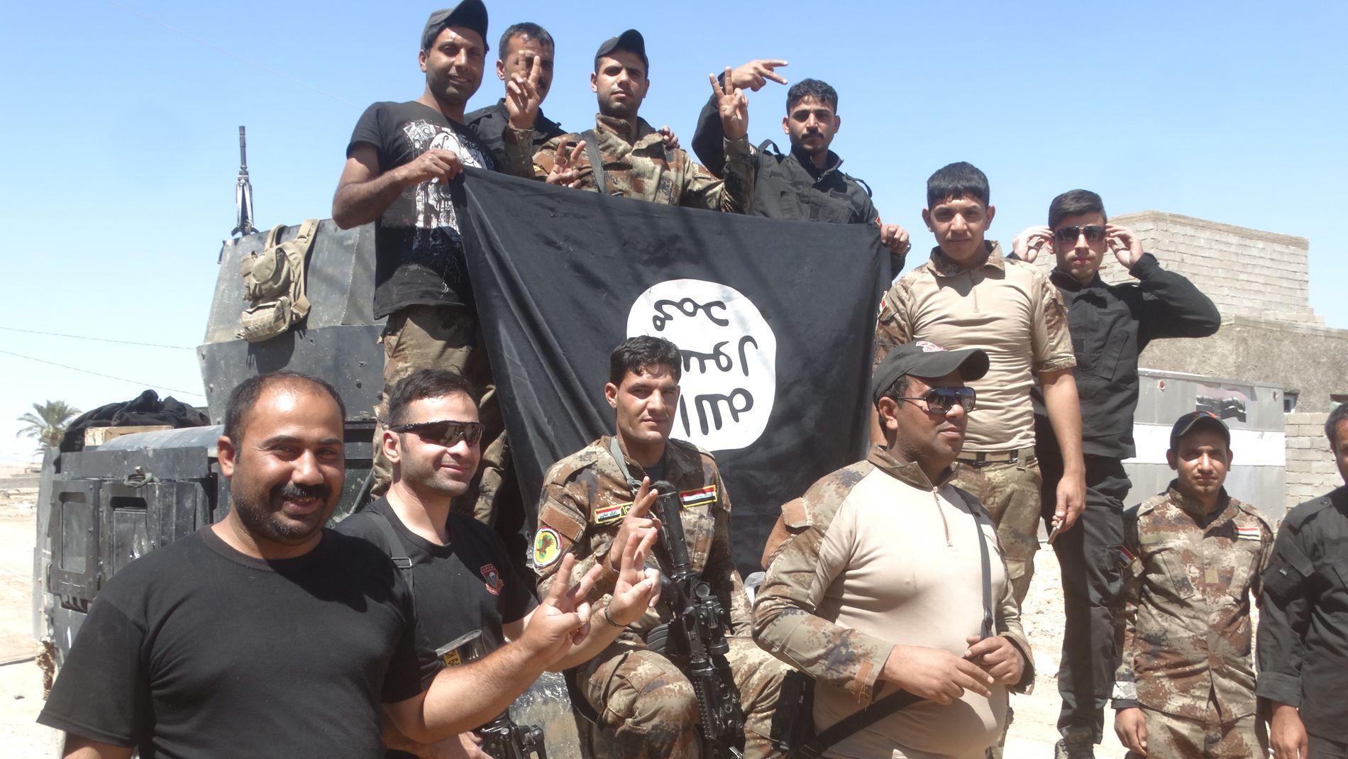 FORNØYDE: Irakiske sikkerhetsstyrker med et IS-flagg de har tatt ned i Heet i Anbar-provinsen.